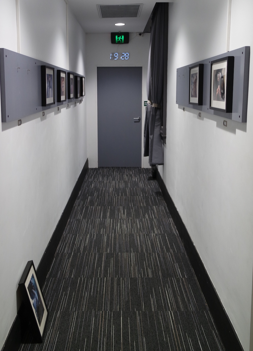 A long hallway with pictures mounted on the walls, an a picture on the floor leaned against the wall. The opposite wall has a door with a clock over it.