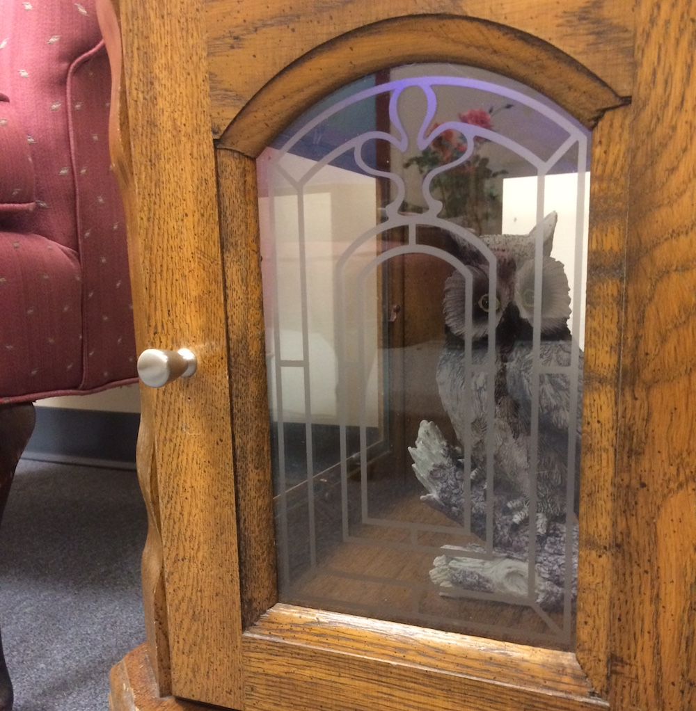 A wood and glass cabinet with an owl statue inside.