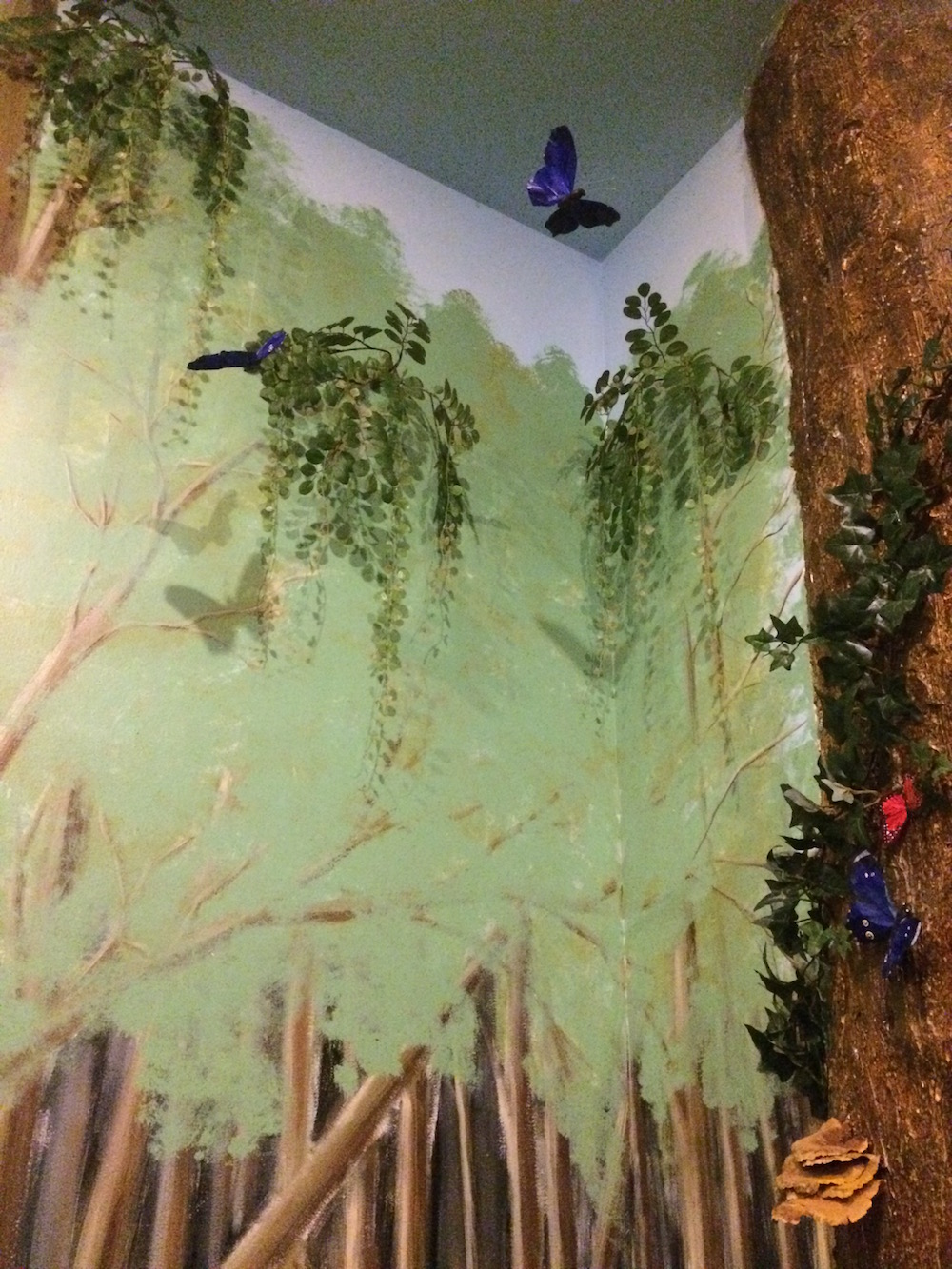 Wall painted to look like a forrest. There's a tree and butterflies.