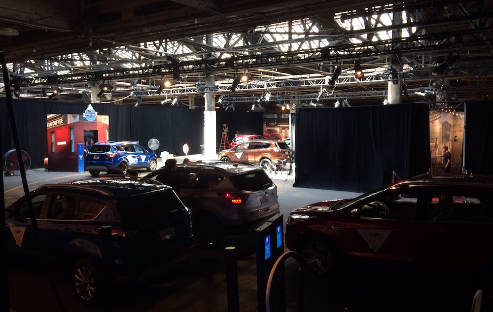 A small fleet of Ford Escapes is in the foreground, the coffee shop stage is in the background.