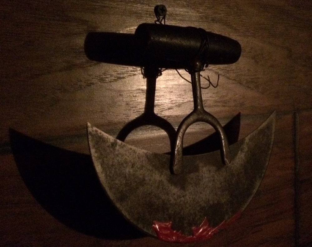 A sharp torture implement hanging from a wooden wall, with blood painted onto the edge.