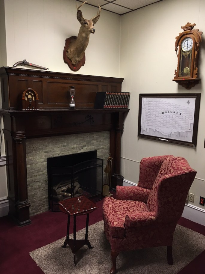 In-game: An old study with a large chair beside a fireplace. A taxidermied buck head hangs on the wall, along with a flintlock pistol.