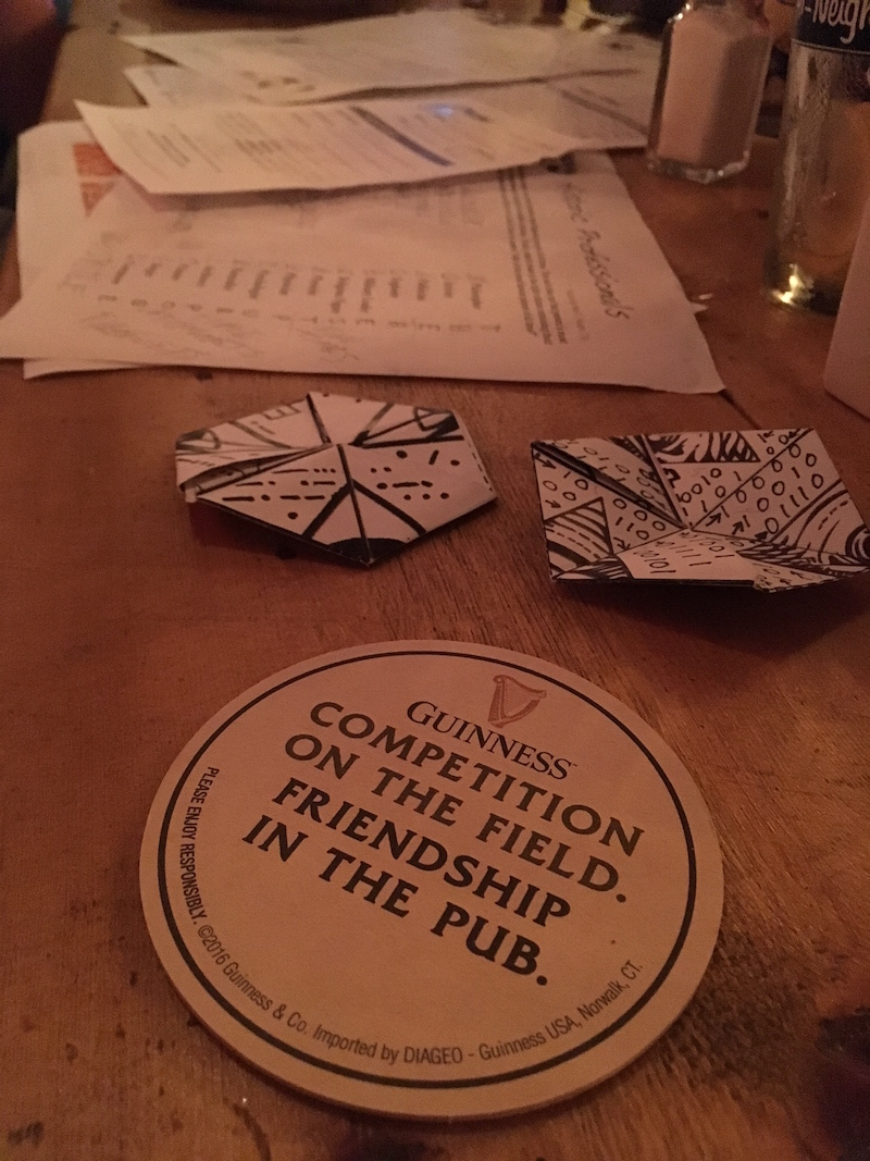 """A coaster that reads, """"Guiness: Competiton on the field. Friendship in the pub."""" rests in front of a variety of paper puzzles."""