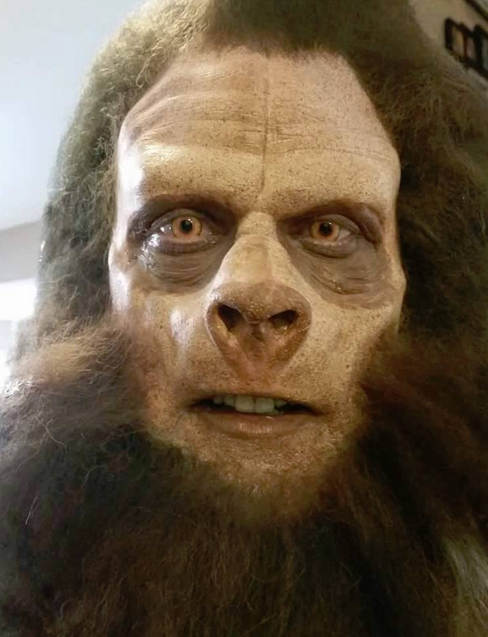 Photo of a man done up in intricate makeup to look like a sasquatch.
