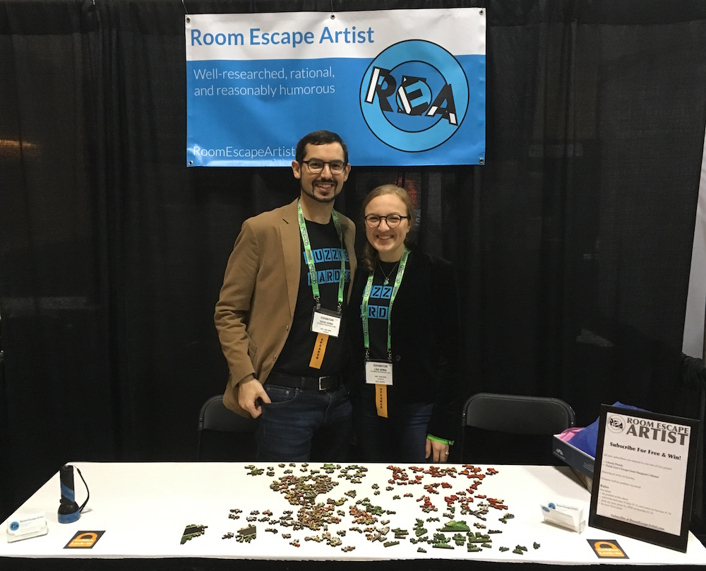 "Lisa and David standing behind their booth at the conference. Their banner in the background, and an unsolved puzzle in the foreground. They are wearing their ""Puzzle Harder"" t-shirts."