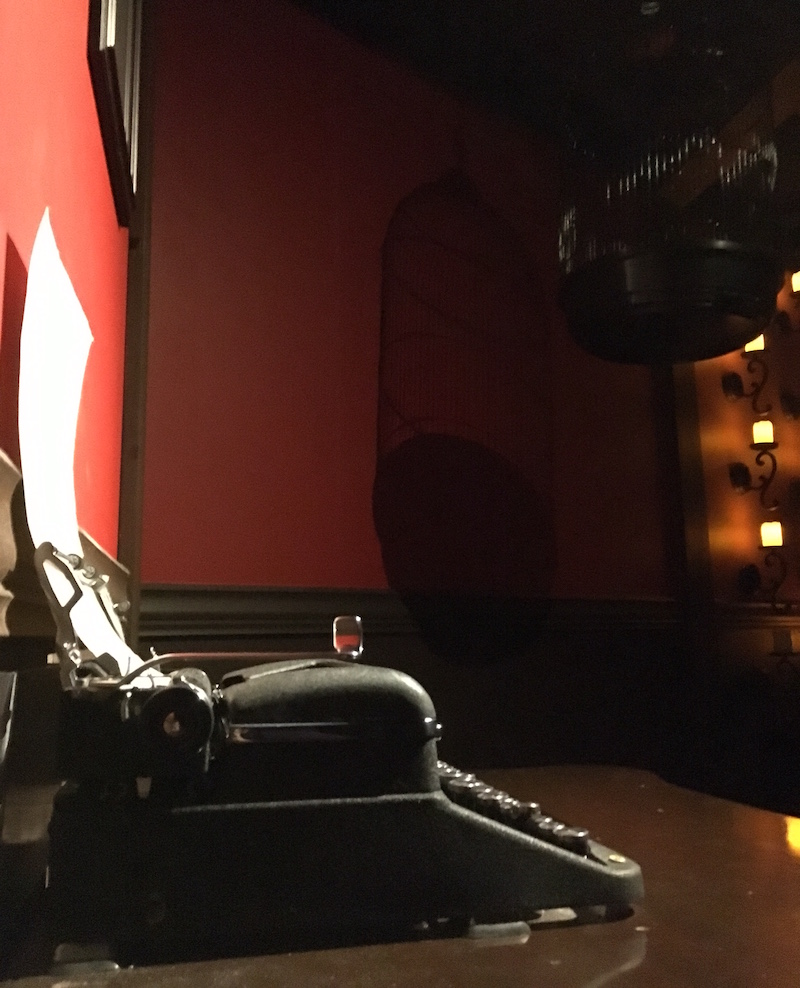 A dimly lit room with red walls. A typewriter sits in the foreground, dramtically lit. A bid cage hangs in the background illuminated by a series of wall-mounted candles.