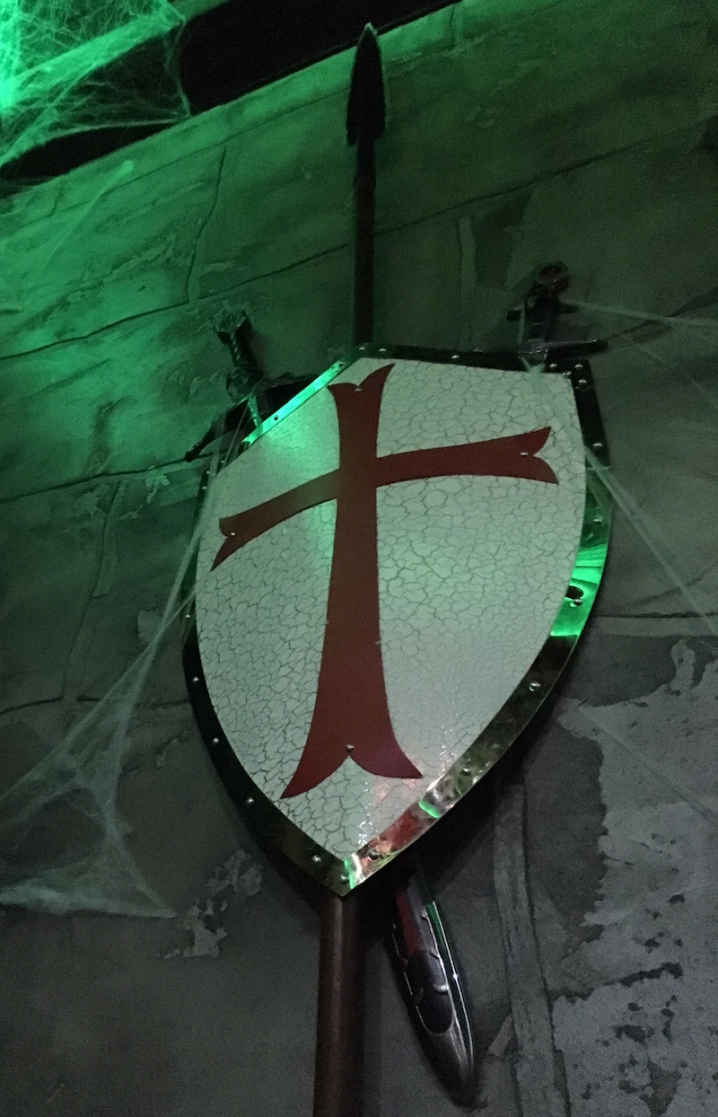 A shield, two swords, and a speak mounted to the wall of a castle.