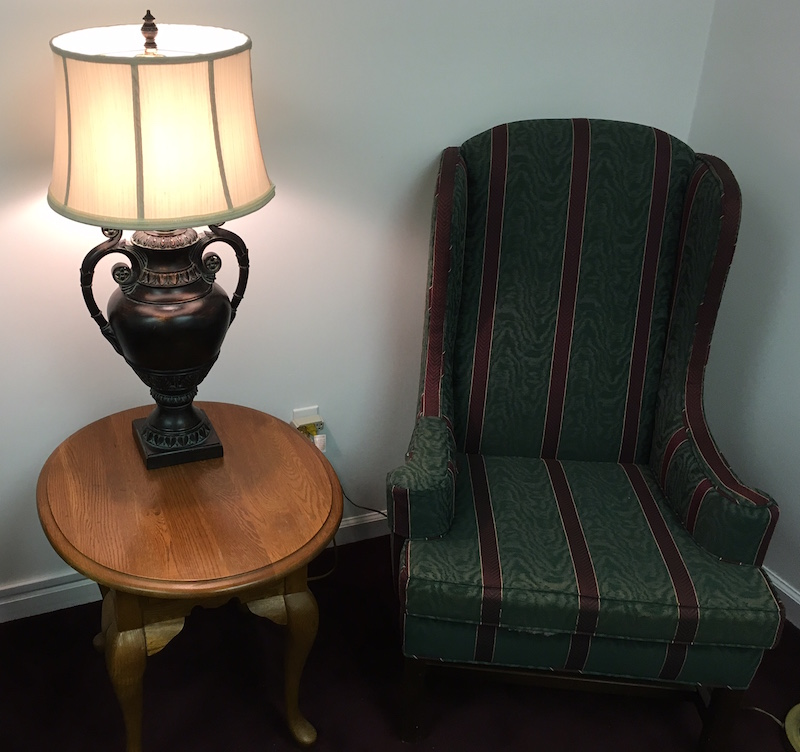A boring looking room. A chair sits beside a small table with a lamp resting on it.