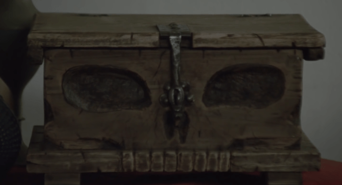 """Trailer screen shot of a wooden box dubbed, """"The Skull Box."""""""