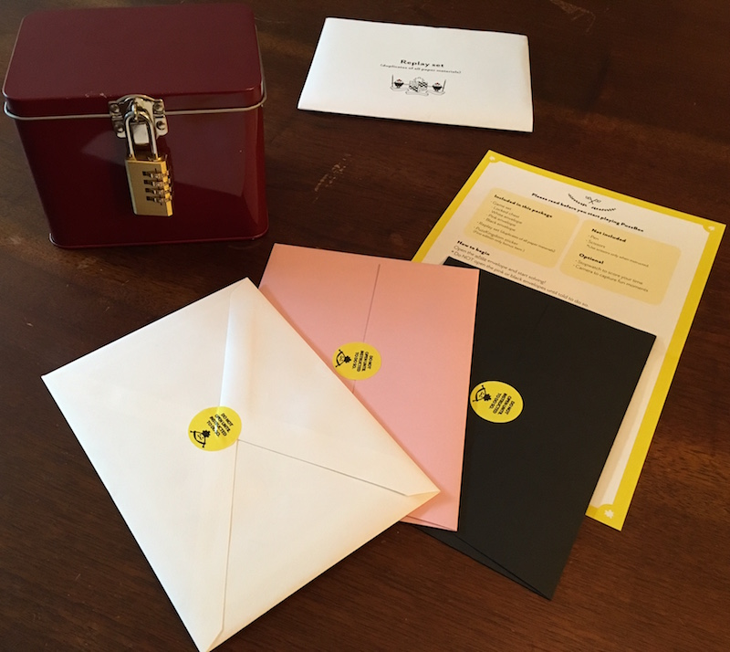 The entire game's contents. A lockbox, three envelopes, a yellow sheet of paper, and a replay set.