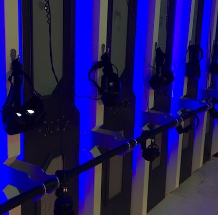 In-game, a glowing blue wall with a series of Oculus Rift headsets hanging from it.