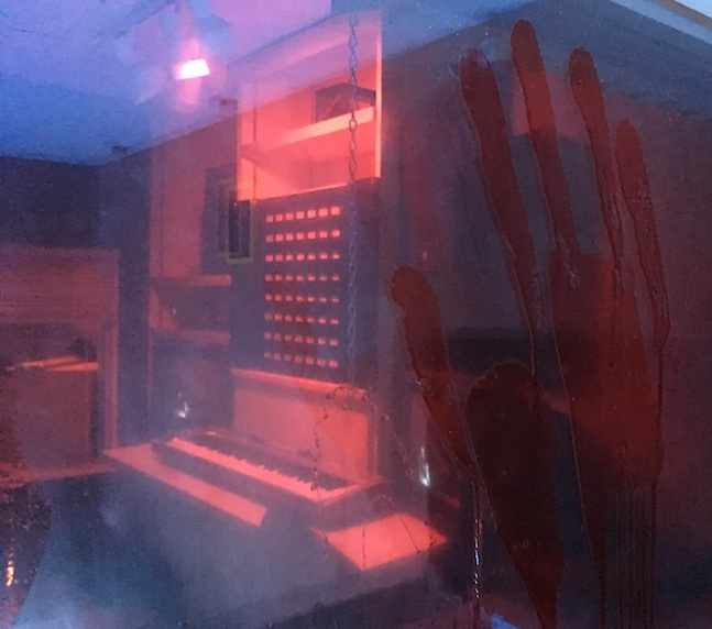 In-game, a bloody handprint on glass, behind it is a recording room with a keyboard and other equipment.