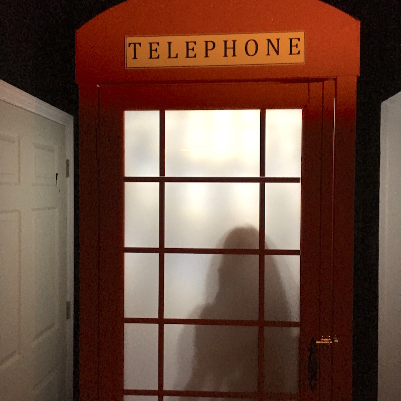 Game exterior, a red phone booth with frosted glass. The silhouette of a person stands behind the glass.