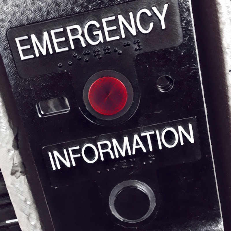 """Black and white image of an subway help panel. """"Emergency"""" has a glowing red button. """"Information"""" has a black button."""
