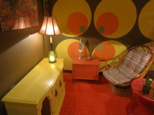 In-game. A 1970s living room with burnt orange shag carpet and a lime green sideboard.