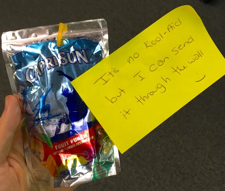"""A CapriSun with a post it that reads, """"It's no Kool-Aid but I can send it through the wall :)"""