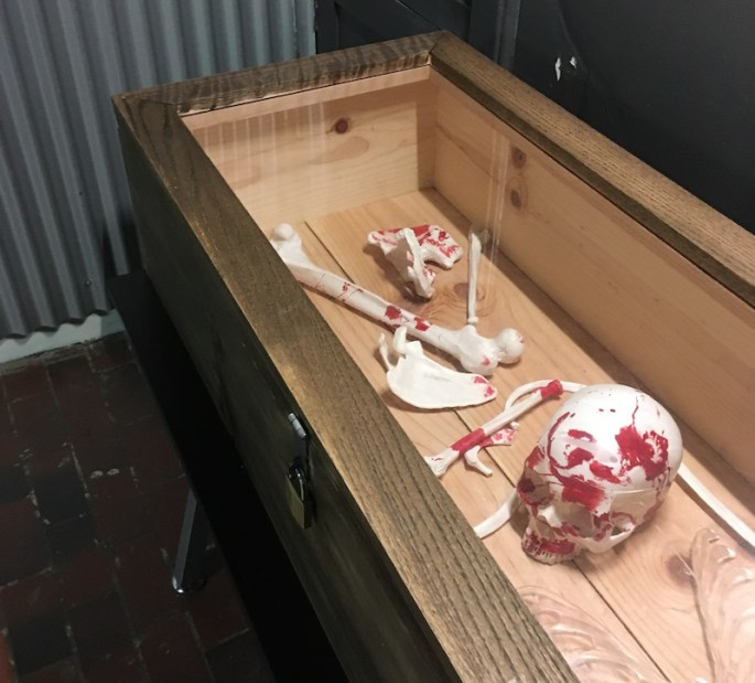 In-game: A coffin with a transparent top. Inside are bloodied bones.