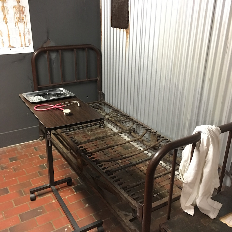 In-game: Corrugated aluminum wall, a brick floor, and a rusty bed with medical equipment on a table beside it.