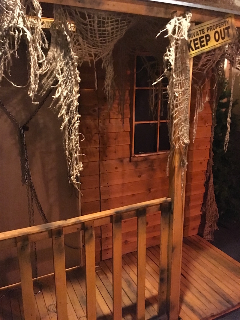 In-game: The exterior of a wood cabin. The door is chained shut, and the window blackened. A sign reads,