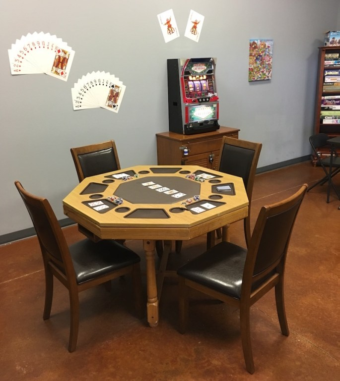 In game: a card table with a game of poker in progress sits in the foreground, assorted games and gaming related things reside in the background.