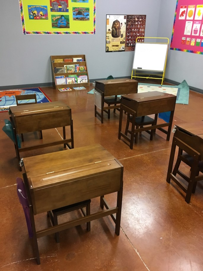 In-game, small school desks set in a classroom with brightly colored posters on the walls.