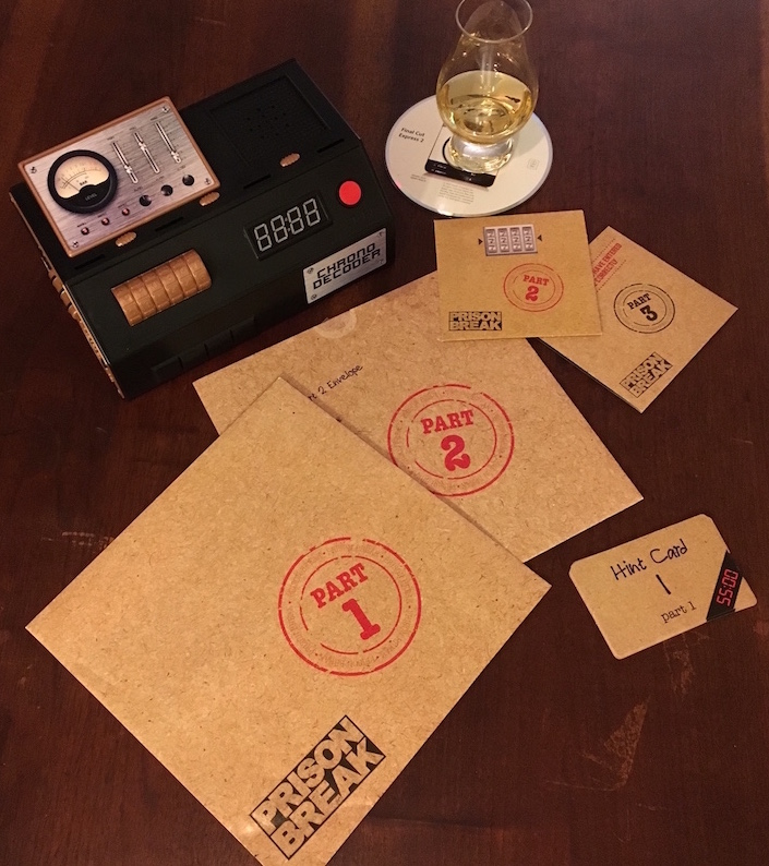 The Chrono Decoder, hint cards, and all game envelopes for Prison Break. A snifter of whiskey sits on a CD of Final Cut Express 2.