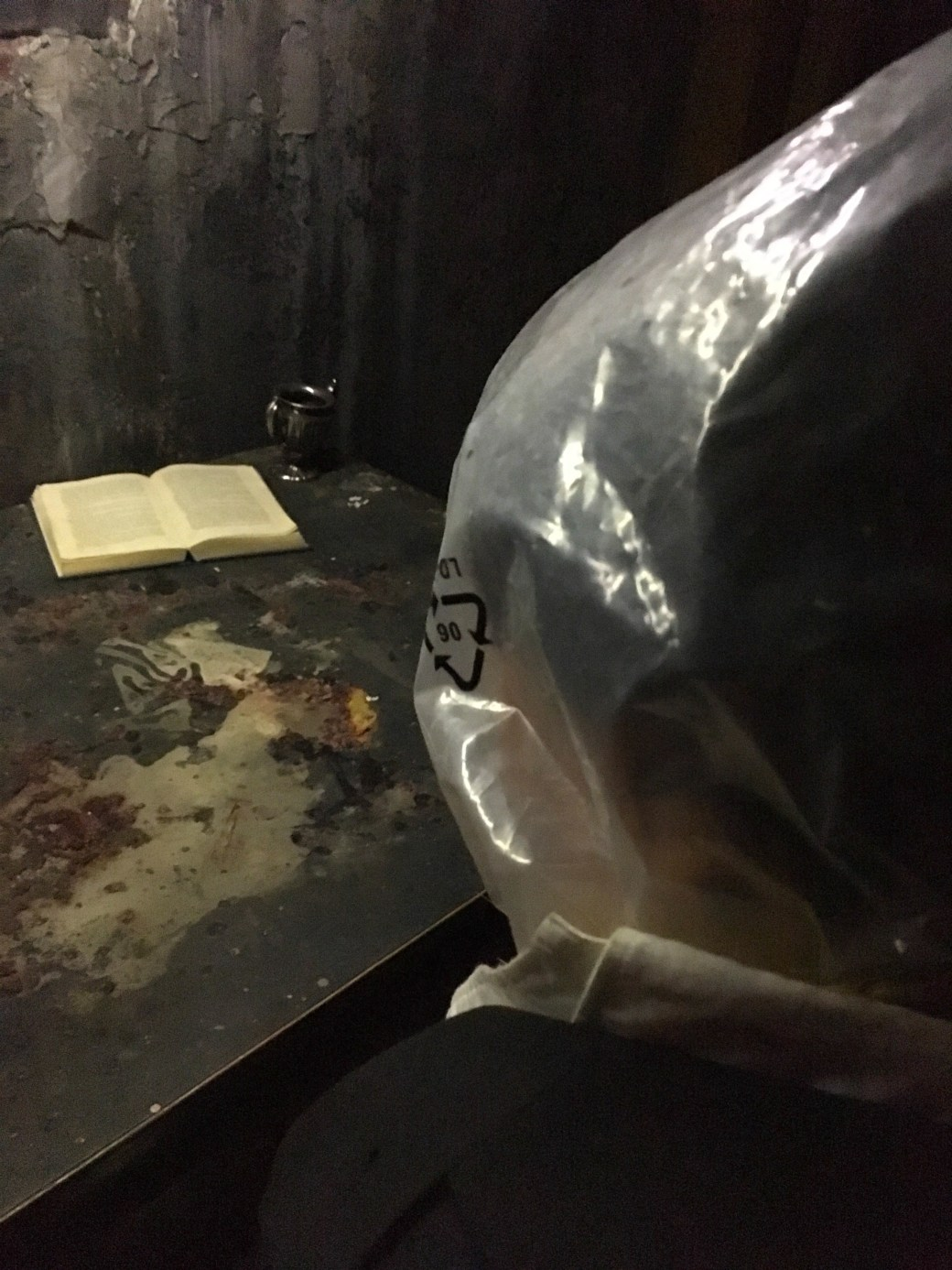 In-game: A man with a bag over his head at a grimy desk.