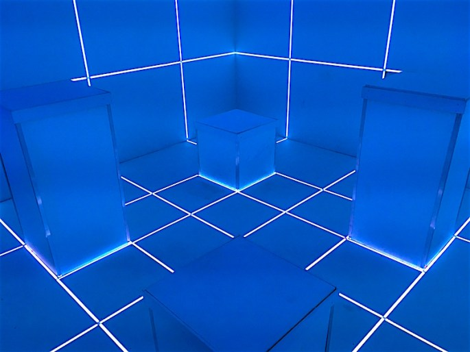In-game: A surreal white room with pillars of varying height. The room is split into small squares by blue LED strips that illuminate the entire space. It looks very futuristic.