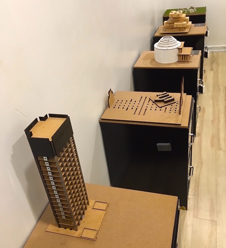 In-game: A series of filing cabinet pedestals, each with a different building model puzzle atop it.