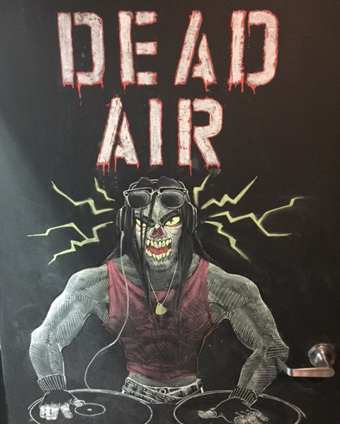 """In-game: Door art of a zombie at a turntable. It reads """"DEAD AIR"""""""