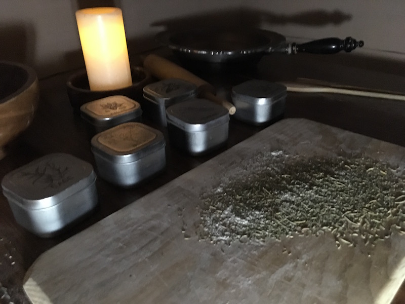 In-game: A table with a cutting board, herbs, and other cooking utensils and ingredients lit by candle.