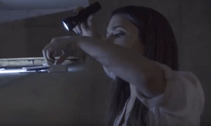 Screengrab from the video: A female escape room player in a dark room with a flashlight. She is inspecting an item on a high shelf.
