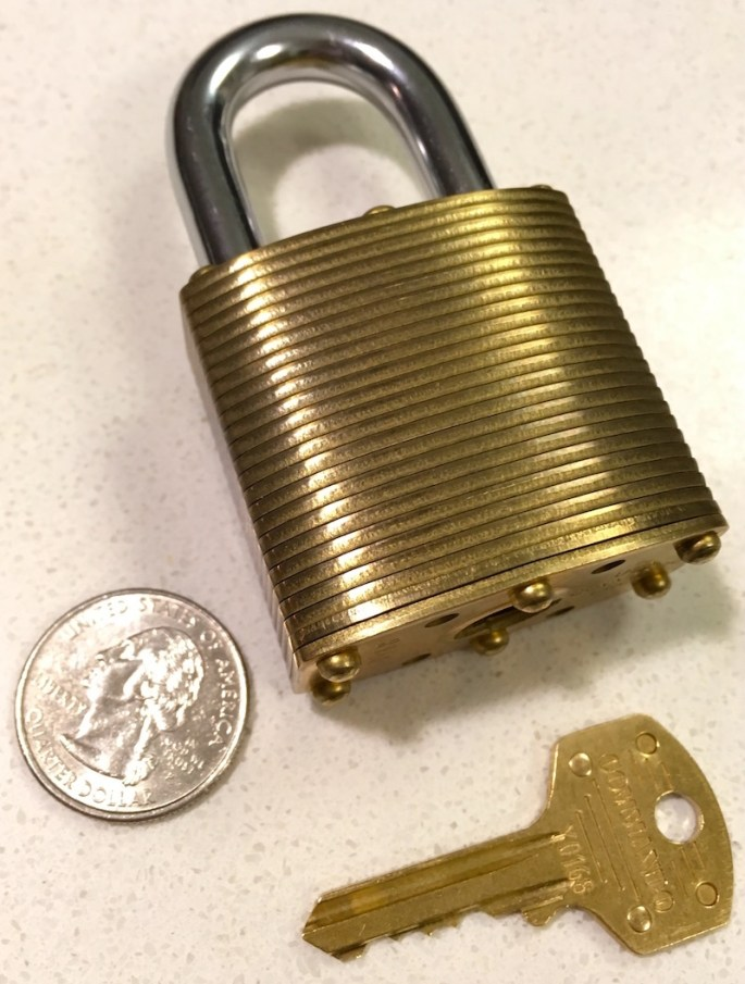 The Commando Lock Marine Brass and it's key in comparison to a quarter.