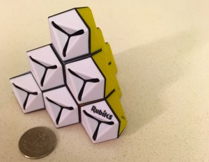 Assembled Rubik's Triamid with the white and yellow faces exposed. A quarter sits beside it to show that it is a reasonably large puzzle.