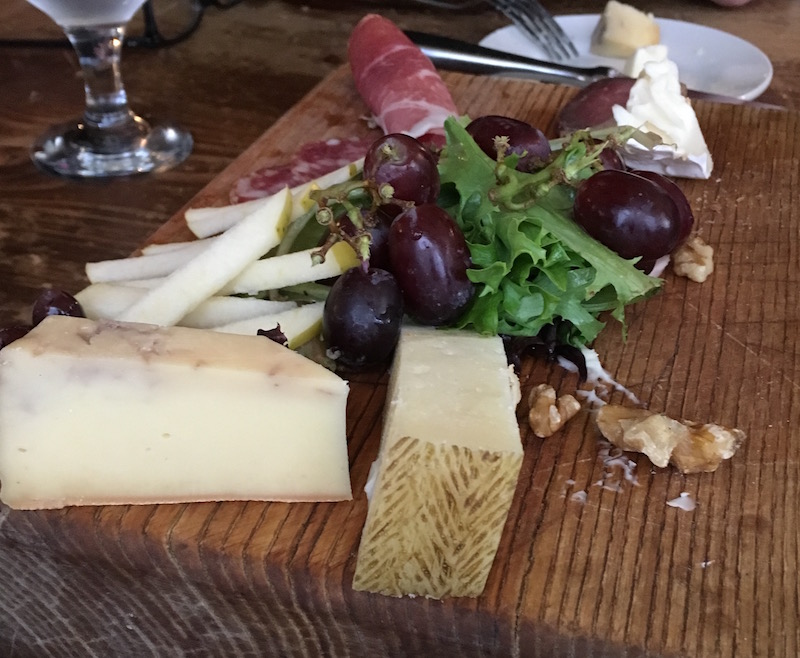 A have eaten plate of food including varies cheeses, greens, fruit, and meat.