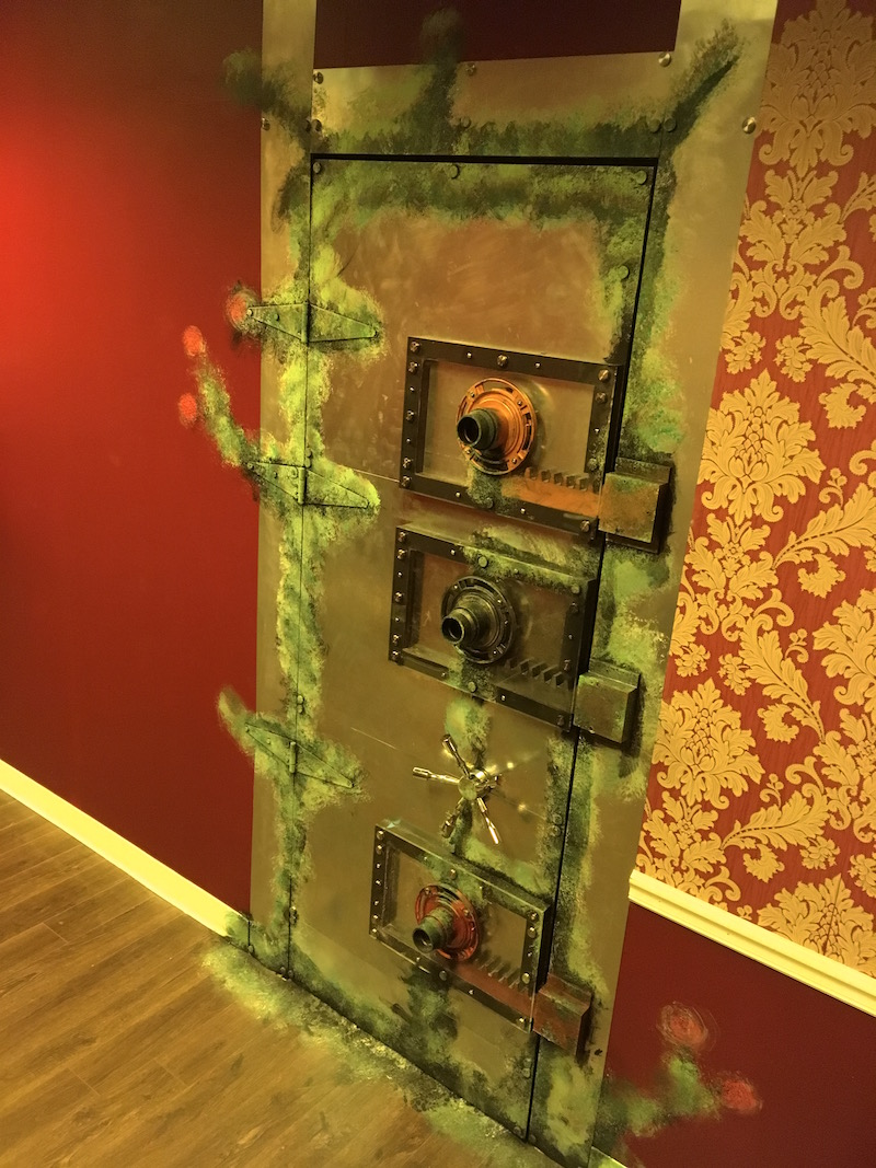 In game: A big metal, vault door with a series of elaborate mechanical locking mechanisms and strange green weathering.