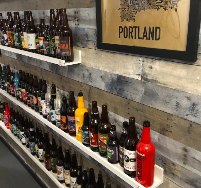 In-game: A wooden wall with long narrow shelves covered in local Portland beer bottles.