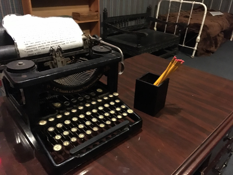In-game: An old typewriter atop a desk in an old hotel room.