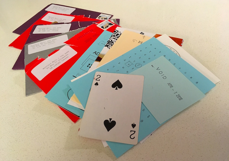 Photo of 5 opened letters and a pile of assorted puzzle material including a partial QR code, a 2 of spades, and a cipher grid.