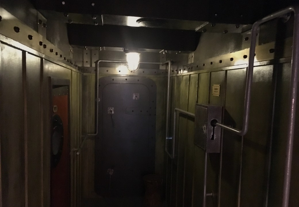 In-game: A hallway with metal walls, doors, and pipes.