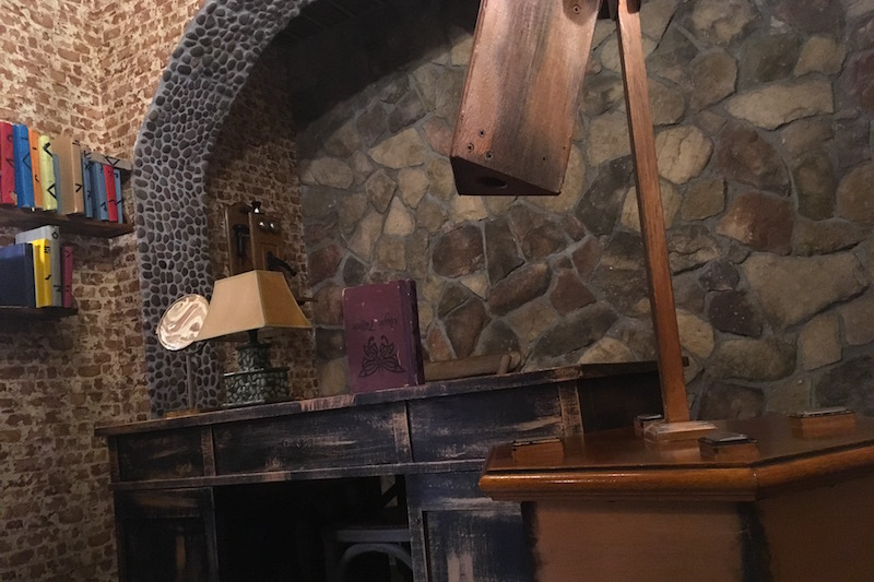 In-game: A wizard's study with strange books,a wooden desk, stone walls, and a strange telescope.
