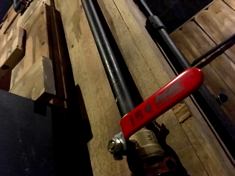 In-game: A wooden wall with pipes and a big red valve mounted to it.