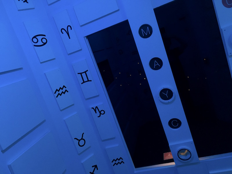 In game: A stark white, lit blue time ship with astrological symbols on the walls.