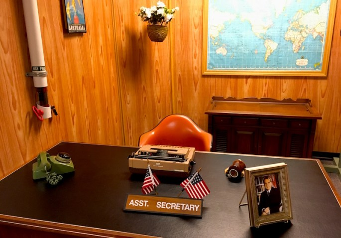 In-game: The Assistant secretary's desk in a wood paneled 1970s bureaucrat's office. A photo of Richard Nixon sits on his desk.