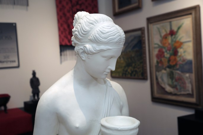 In game: A white statue of a nude woman holding a bowl in the middle of an art gallery. Paintings and statues rest in the background.
