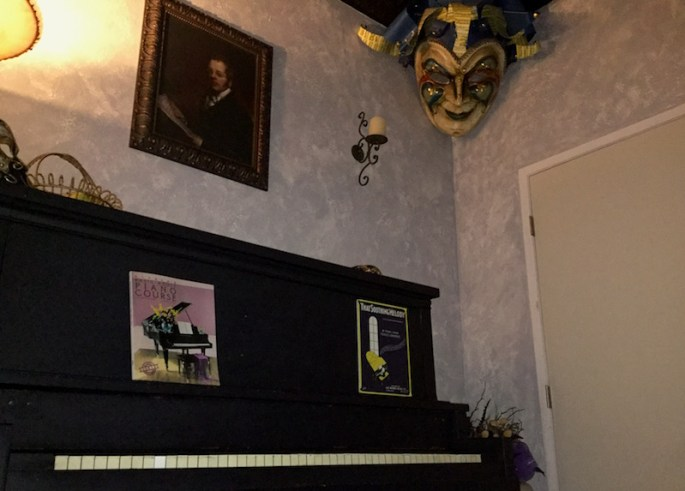 In-game: A large gestures mask hangs in the upper corner of a room above a black piano.