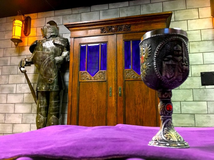 In-game: A chalice sitting on a purple clothed table, with a suit of armor and confessional booth in the background.