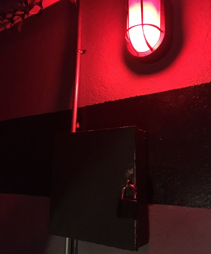 In-game, a loked wall-mounted box illuminated by a red light.