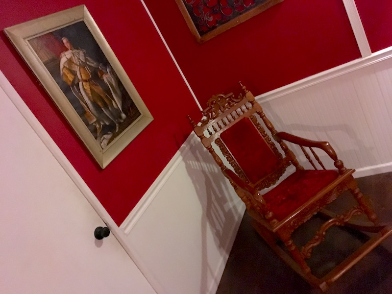 In game: A regal red wooden rocking chair beside a painting of King George III.