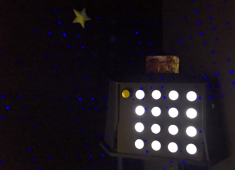 A dark room filled with speckled blue stars, a large stick-on star, and a console with 16 glowing white buttons.